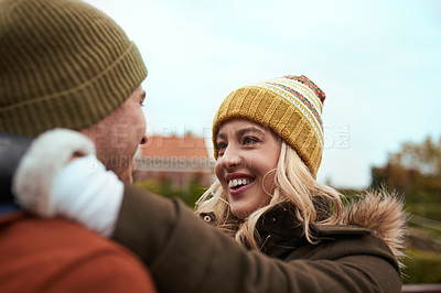 Buy stock photo Cropped shot of an affectionate young woman smiling at her boyfriend while standing in a park in late autumn