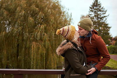 Buy stock photo Cropped shot of an affectionate young couple kissing while spending time together in a park in late autumn