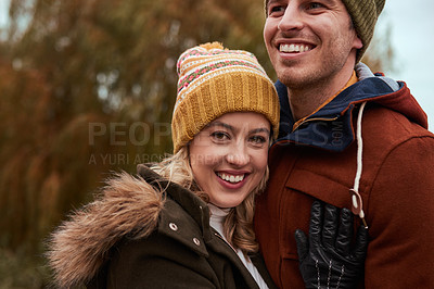 Buy stock photo Cropped shot of an affectionate young couple smiling while spending time together in a park in late autumn