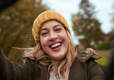 Buy stock photo Cropped portrait of an attractive young woman taking a selfie while out in the park in late autumn