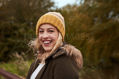 Buy stock photo Cropped portrait of an attractive young woman smiling while standing in a park in late autumn