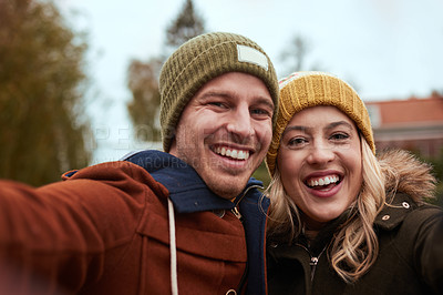 Buy stock photo Cropped portrait of an affectionate young couple taking a selfie together while standing in a park in late autumn