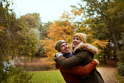 Buy stock photo Cropped shot of an affectionate young couple spending time together in a park in late autumn