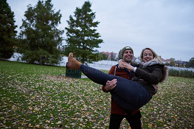 Buy stock photo Cropped portrait of an affectionate young man lifting his girlfriend in a park in late autumn