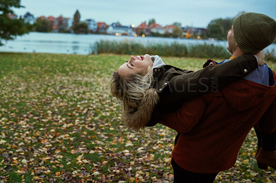 Buy stock photo Cropped shot of an affectionate young woman being lifted by her boyfriend in a park in late autumn