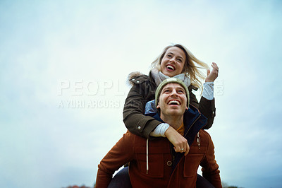 Buy stock photo Cropped shot of an affectionate young man piggybacking his girlfriend in a park in late autumn