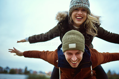 Buy stock photo Cropped portrait of an affectionate young man piggybacking his girlfriend in a park in late autumn