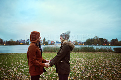 Buy stock photo Cropped shot of an affectionate young couple holding hands while standing in park in late autumn