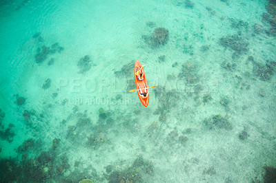 Buy stock photo High angle shot of an adventurous young couple canoeing together in the beautiful oceans of Indonesia