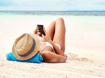 Buy stock photo Rearview shot of a young woman using a smartphone while relaxing on the beach