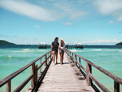 Buy stock photo Shot of a carefree young couple walking on a jetty together next to the ocean during the day