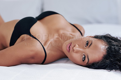 Buy stock photo Cropped portrait of a gorgeous young woman posing in lingerie on her bed at home