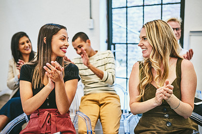 Buy stock photo Cropped shot of two attractive young businesswomen smiling at each other while clapping their hands during a seminar