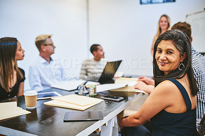 Buy stock photo Cropped portrait of an attractive  middle aged businesswoman smiling during a seminar in a modern office