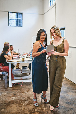 Buy stock photo Full length shot of two attractive businesswomen using a digital tablet in an office with their colleagues in the background