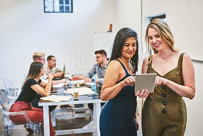 Buy stock photo Cropped shot of two attractive businesswomen using a digital tablet in an office with their colleagues in the background