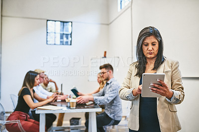 Buy stock photo Cropped shot of an attractive middle aged businesswoman using a digital tablet in an office with her colleagues in the background