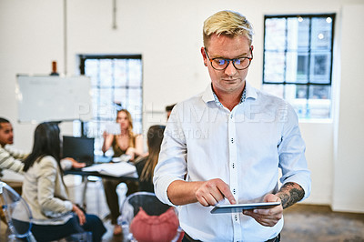 Buy stock photo Cropped shot of a handsome young businessman using a digital tablet in an office with his colleagues in the background
