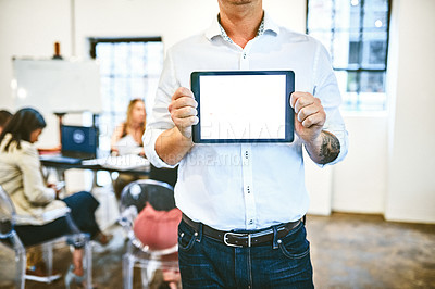 Buy stock photo Cropped shot of an unrecognizable businessman holding up a digital tablet in an office with his colleagues in the background