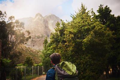 Buy stock photo Rearview shot of a young man backpacking outdoors