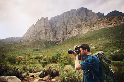 Buy stock photo Shot of a young man taking photos while hiking through the mountains