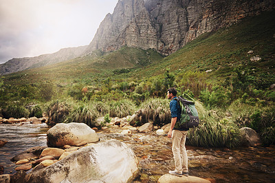 Buy stock photo Shot of a young man standing at a lake while hiking through the mountains