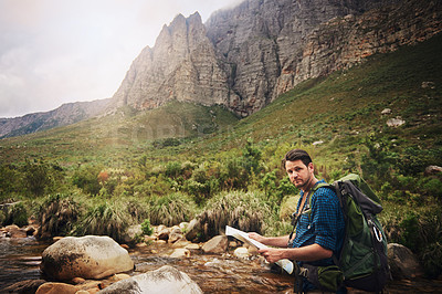 Buy stock photo Portrait of a young man using a map while hiking through the mountains