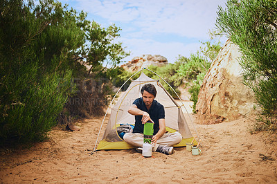 Buy stock photo Shot of a young man using  a camping stove in the wilderness