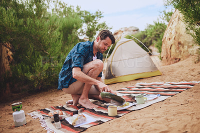 Buy stock photo Shot of a young man preparing food while camping in the wilderness