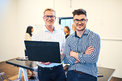 Buy stock photo Portrait of two businessmen using a laptop during a meeting with colleagues in a modern office