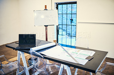 Buy stock photo Shot of a blueprint and various other business tools on a table in a modern office