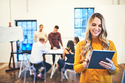 Buy stock photo Shot of a young businesswoman using a digital tablet with her team in the background of a modern office
