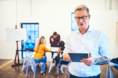 Buy stock photo Shot of a businessman using a digital tablet with his team in the background of a modern office