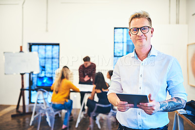 Buy stock photo Portrait of a businessman using a digital tablet with his team in the background of a modern office