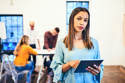 Buy stock photo Portrait of a young businesswoman using a digital tablet with her team in the background of a modern office