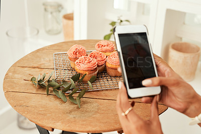 Buy stock photo Cropped shot of an unrecognizable businesswoman using her cellphone to take pictures of cupcakes for her blog