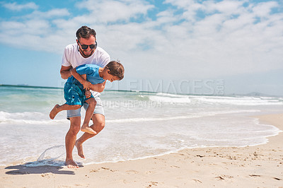 Buy stock photo Shot of an adorable little boy having fun with his father at the beach