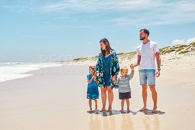 Buy stock photo Shot of a happy young family going for a relaxing walk along the beach