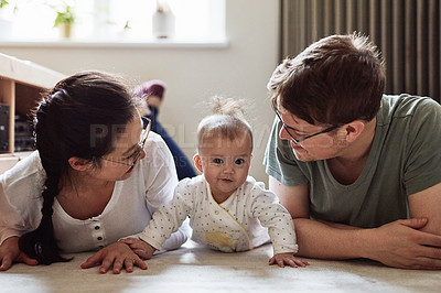 Buy stock photo Shot of a couple bonding with their infant daughter at home