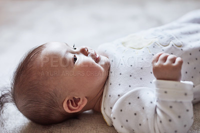 Buy stock photo Cropped shot of an adorable baby girl lying on her back