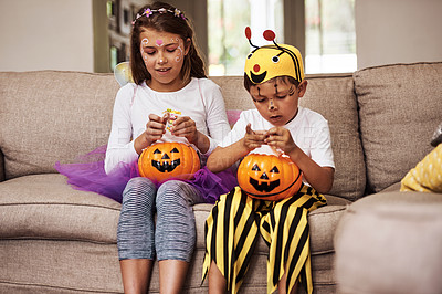 Buy stock photo Cropped shot of a young brother and sister eating their Halloween candy while sitting on their sofa at home