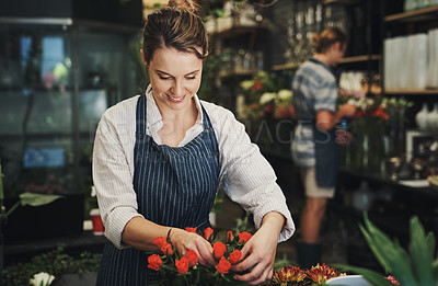 Buy stock photo Shot of an attractive young florist arranging flowers inside a plant nursery with her colleague also working in the background