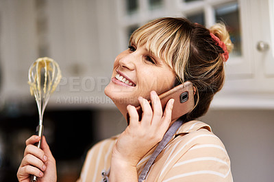 Buy stock photo Shot of a woman holding a whisk while talking on her cellphone
