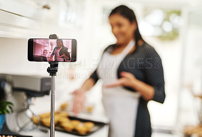 Buy stock photo Cropped shot of a woman being recorded on a cellphone while baking in the kitchen