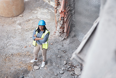 Buy stock photo High angle portrait of an attractive young female construction worker standing with her arms folded on site