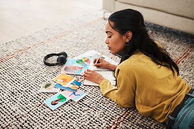 Buy stock photo Cropped shot of an attractive young businesswoman lying on her living room floor and sorting through polaroids for her blog