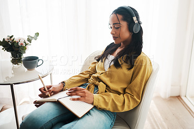 Buy stock photo Cropped shot of an attractive young businesswoman sitting in her living room and writing notes while listening to music