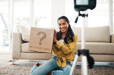 Buy stock photo Cropped shot of an attractive young businesswoman sitting in her living room and holding up a mystery box while vlogging