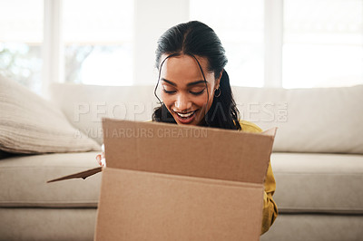 Buy stock photo Cropped shot of an attractive young businesswoman sitting alone on her living room floor and opening up a mystery box