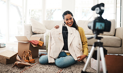 Buy stock photo Full length shot of an attractive young businesswoman sitting in her living room and showing new clothing for her vlog